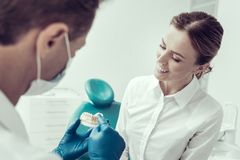 Smiling patient consulting her dentist royalty free stock image