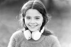 She looks like a music lover. Adorable little girl outdoor. Little girl child wearing headphones. Happy child enjoy stock photo