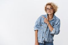 Looks suspicious what you think. Portrait of doubtful unsure and hesitant good-looking stylish girlfriend in denim. Jacket and glasses pursing chin in royalty free stock images