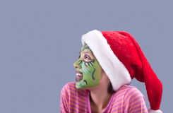Looks to the side. A young girl  wears a Santa hat and has face paint similar to the Grinch Royalty Free Stock Photos