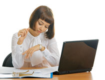 Looks on the watches. Girl in the office with the computer and working papers. She looks on the watches Stock Photo