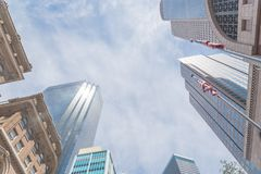 Lookup view of Dallas skylines and American flag under cloud blue sky royalty free stock photo