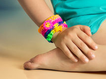 Loom bracelets on child hand close up.Rubber colorful wrist acce Stock Images