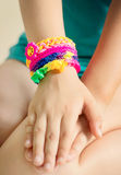 Loom bracelets on child hand.Rubber colorful wrist accessories. Stock Image