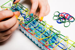 Loom bracelets. Young girl making loom bracelets,  on a white background. Young fashion concept Royalty Free Stock Image