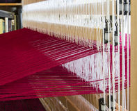 A loom set up with red wool warp threads ready for weaving Stock Photography