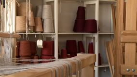 A loom and several cones of yarn on a nearby shelf. A room with a loom, and several cones of various colors of yarn on a shelf in the background stock footage