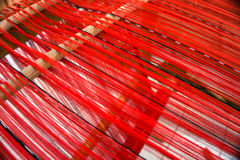 Loom strung with red threads for weaving Stock Photo