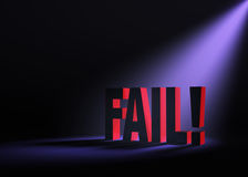 Looming Fail. Angled spotlight backlighting and revealing red FAIL on a dark background Royalty Free Stock Photography