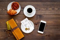 Loonsrekening bij koffie door kaart Beurs, rekening en betaalpas dichtbij koffie en croissant op de donkere houten mening van de  Stock Foto