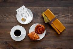 Loonsrekening bij koffie door kaart Beurs, rekening en betaalpas dichtbij koffie en croissant op de donkere houten mening van de  Stock Afbeeldingen