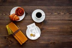 Loonsrekening bij koffie door kaart Beurs, rekening en betaalpas dichtbij koffie en croissant op de donkere houten mening van de  Stock Fotografie