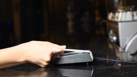 Loonsrekening met telefoon Vrouwelijke cliënt die smartphone gebruiken om via betalingsterminal bij barteller te betalen Draadloo stock video