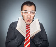 Loony professor. Cheerful man with book. Loony professor, on gray background, studio shot royalty free stock photography