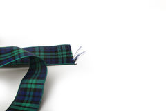 Loop of Blue and green Tartan Ribbon with freyed edges on white background. Photograph of a Looped strip of Blue and green Tartan Ribbon with freyed edges on Stock Image