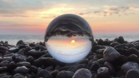 Loop cinemagraph crystal ball on the beach stones sunset, wonderful landscape. Loop cinemagraph crystall ball on the beach stones sunset, wonderful landscape stock video footage