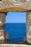 Loop-hole with sea view. Ancient stone rectangular loop-hole with sea view Stock Image