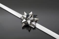 Loop of shining gift. On dark bottom Royalty Free Stock Photo