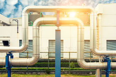 Loop steam pipeline on cooling tower background and sunshine., Insulation pipe. Royalty Free Stock Images