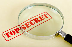 Loop is on 'top secret'. Magnifying glass is on top secret inscription Stock Photos