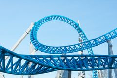 Loop and turn on a blue roller coaster in an amusement park. Loop and turn on a blue roller coaster in an amusement park royalty free stock photo
