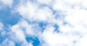 Loop of white clouds over blue sky time lapse stock video footage