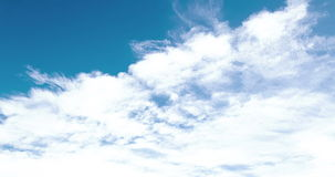 Loop of white clouds over blue sky time lapse stock footage