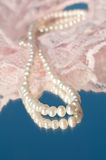 Loop of white natural pearls on pink lace. And reflection on blue Stock Images