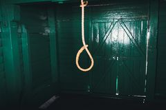 Loop of white rope on a black background. Loop of white rope on a dark background of a wooden wall of green color. the concept of suicide. hangman in the old Royalty Free Stock Photos