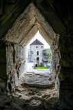 Loophole of old castle wall. Loophole in fortifications of 14th century Kamianets-Podilskyi Castle, Ukraine. Blurred view to the courtyard of medieval fortress royalty free stock photography