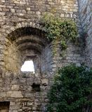 The loophole in the wall of the fortress of Brescia. Loophole in an ancient stone wall overgrown with ivy stock photo