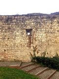 The loophole in the wall of the fortress of Brescia. Loophole in the old stone wall in the courtyard of the fortress Brescia stock photo