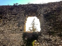 The loophole in the wall of the fortress of Brescia. Loophole in the old stone wall in the courtyard of the fortress Brescia, through which you can see the tree royalty free stock photo