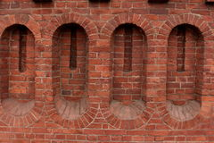 Loopholes in a fortress wall. Red brick fortress wall background close to Stock Photography