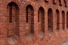Loopholes in a fortress wall. Red brick fortress wall background close to Royalty Free Stock Photography