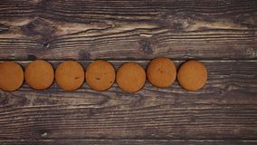 Looping cookies on wooden background. Stop motion. Animation video stock footage