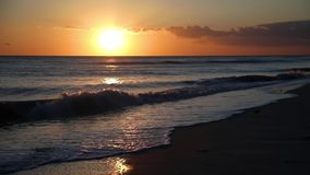 Sunset waves looping video footage. Looping video features waves rolling gently onto the sandy beach of Sanibel Island, Florida in the Gulf of Mexico near sunset stock footage