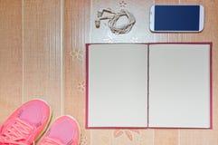 Loopschoen, slimme telefoon, en notitieboekje op de bruine achtergrond Het concept van de planning Stock Afbeeldingen