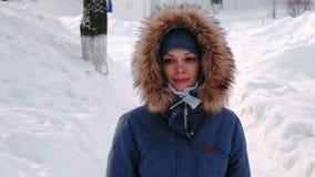 Loopt de close-up glimlachende vrouw in de winterpark in de stad in de loop van de dag in sneeuwweer met dalende sneeuw voorzijde stock videobeelden