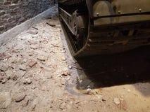 Loopvlakken van oude tank op grond dichtbij bakstenen muur stock afbeelding