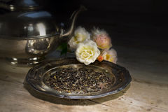 Loose black tea on an old dish, roses and silver teapot on a rus Stock Photo