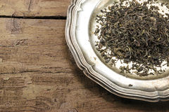 Loose black tea on a silver plate on rustic brown wood Stock Photography