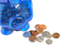 Loose Change. Piggy bank and change on a white background focus is on the loose change Royalty Free Stock Photos