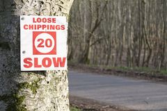 Loose chips 20 mph slow road sign on tree in woodland forest. Uk stock images