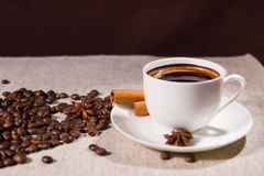 Loose coffee beans beside mug and star anise Stock Photos
