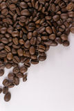 Loose Coffee Beans on White Background. Overhead photograph of random coffee beans on white paper with copy space Royalty Free Stock Photos