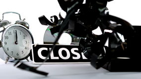 Loose film falling beside closed sign and videos and alarm clock Royalty Free Stock Photography