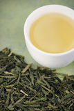 Loose green tea and cup Royalty Free Stock Image