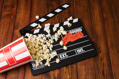 Loose popcorn, striped box, tickets and movie clapper on a wooden background Stock Image
