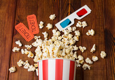 Loose popcorn in striped box, two tickets to the cinema and 3D glasses. On a wooden background Royalty Free Stock Photos